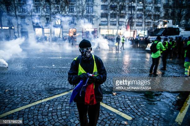 TOPSHOT Protesters wearing yellow vests stand amid smoke of tear gas during a demonstration against rising costs of living they blame on high taxes...