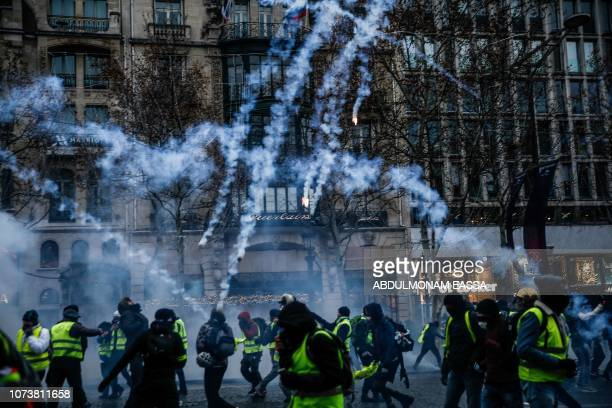 Protesters wearing yellow vests stand amid smoke of tear gas during a demonstration against rising costs of living they blame on high taxes on the...