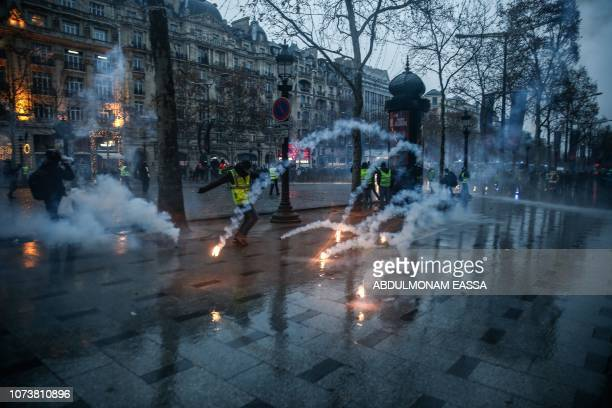 TOPSHOT Protesters wearing yellow vests stand amid tear gas during a demonstration against rising costs of living they blame on high taxes on the...