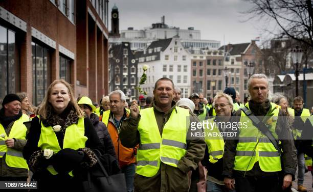 Protesters wearing yellow vests take part in a protest in Amsterdam on December 8 2018 The socalled gilets jaunes protest movement which started in...