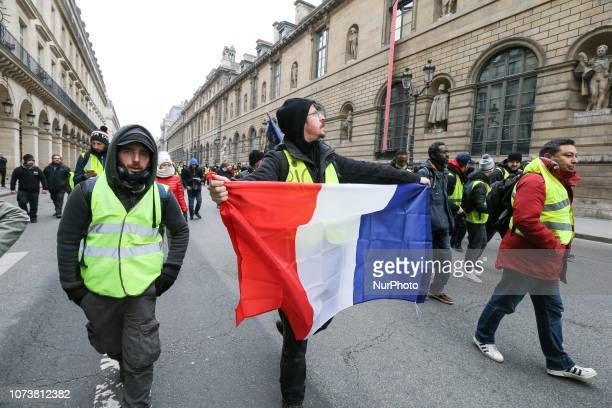 Protesters wearing yellow vests walk in front of the Louvre Museum during a demonstration in Paris on December 15 against rising costs of living...