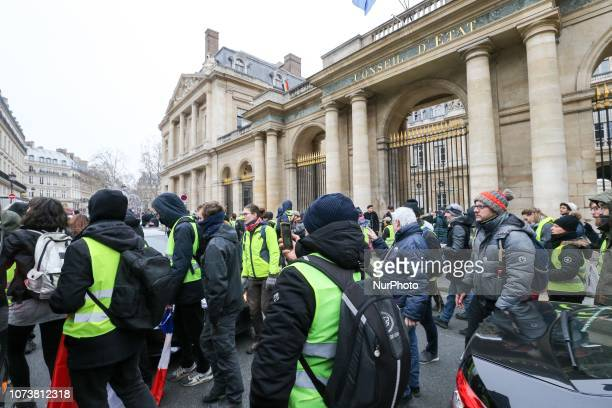 Protesters wearing yellow vests walk in front of the Senate during a demonstration in Paris on December 15 against rising costs of living blamed on...