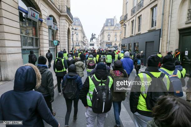 Protesters wearing yellow vests walk in the streets of Paris during a demonstration against rising costs of living blamed on high taxes on December...