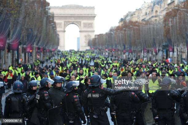 Protesters wearing yellow vests' walk on the Champs Elysees Avenue in Paris France on December 08 2018 during a protest against rising costs of...
