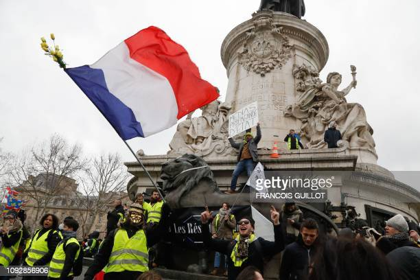 Protesters wearing yellow vests wave the French national flag during a march at Place de la Republique in Parison February 2 called to protest...