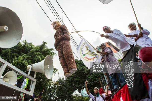 Protesters whip an effigy of Myanmar monk Wirathu as thousands of members of various Indonesian muslim groups demonstrate in support of Myanmar's...
