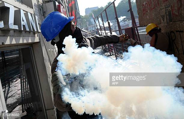 A protesters winds up to throw a smoking canister in Taksim square in Istanbul early on June 11 2013 as protesters and riot police clashed Riot...