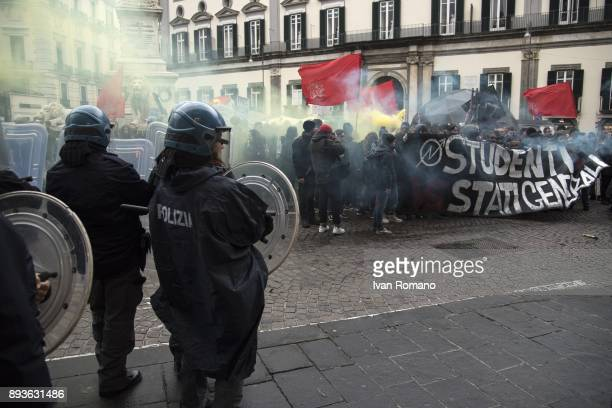 Protesters with a banner and smoke flares near the Confcommercio in front of police in riot gear during demonstrations in the streets of Naples...