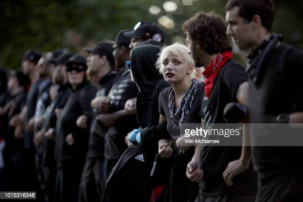Protesters with a group known as Antifa or antifascists link arms at an event on the campus of the University of Virginia organized by the group...