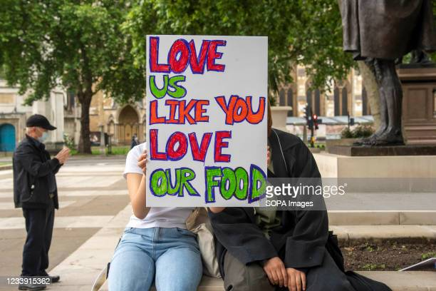 Protesters with a placard saying 'Love us like you love our food' take part during a Stop Asian Hate protest at Parliament Square in London....