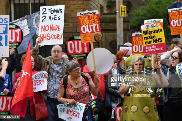 Protesters with antiConservative and anticuts banners and placards including one dressed as a Dalek holding a mask showing the face of Prime Minister...