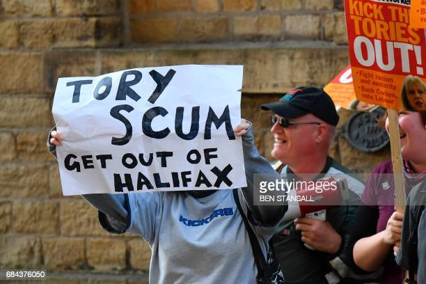 Protesters with banners and antiConservative placards demonstrate outside the venue where Prime Minister Theresa May and government ministers will...