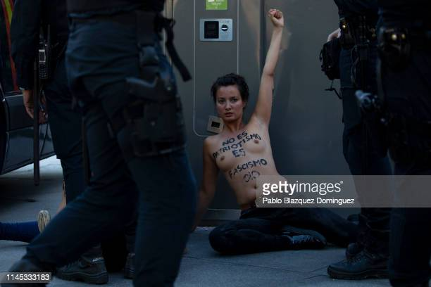 FEMEN protesters with body painting reading 'It is not patriotism It's Fascism' are surrounded by police after disrupting the VOX closing rally on...