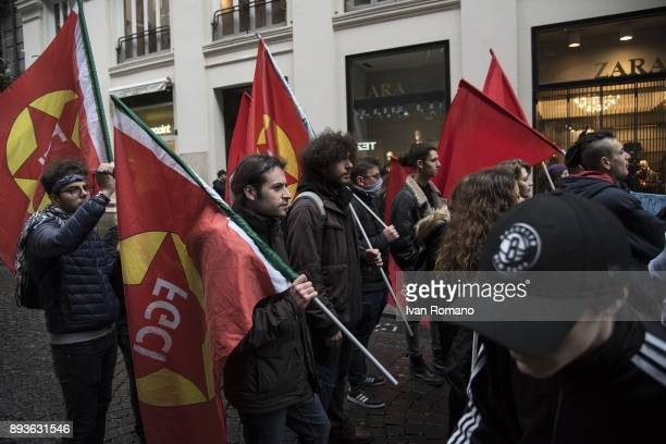 Protesters with flags of the Italian Federation of Young Communists march in a march near a Zara store a company that has joined the alternating...