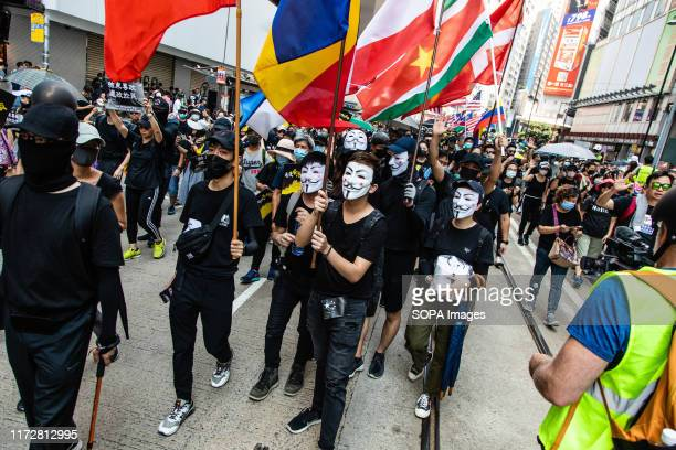 Protesters with Guy Fawkes masks march with flags during the demonstration Entering the 18th week of civil unrest protesters marched on the morning...