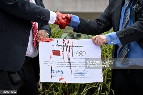 Protesters with masks bearing Chinese President Xi and International Olympic Committee President shake hands in front of the IOC headquarters during...