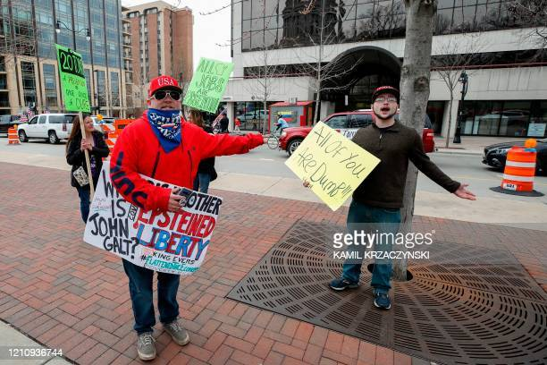 Protesters with opposing views argue during a rally to end the coronavirus shutdown in front of State Capitol in Madison Wisconsin on April 24 2020...