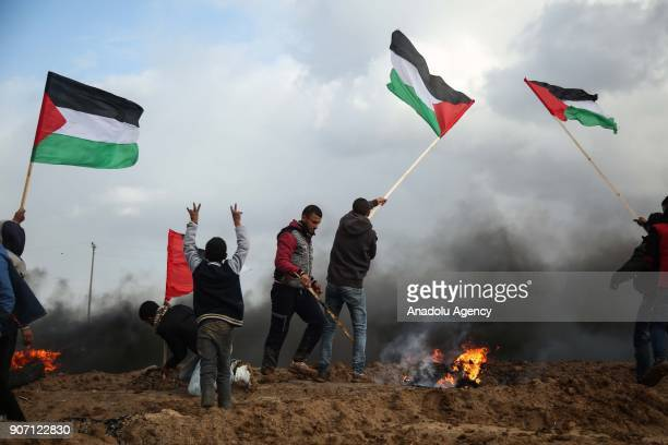 Protesters with Palestinian flags burn tires in response to Israeli forces' intervention in a protest against US decision to recognize Jerusalem as...