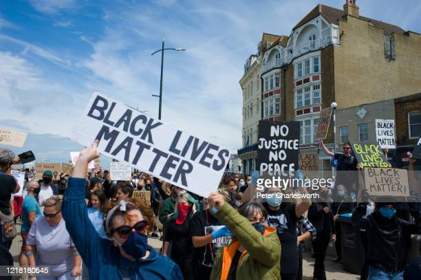 Protesters with placards arrive at the harbour steps. Hundreds of local people joined a Black Lives Matter march - along the coast of one of Englands...