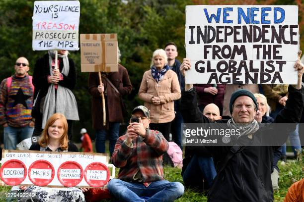 Protesters with placards gather outside the Scottish Parliament entrance to demonstrate against new coronavirus restrictions, face covering rules and...
