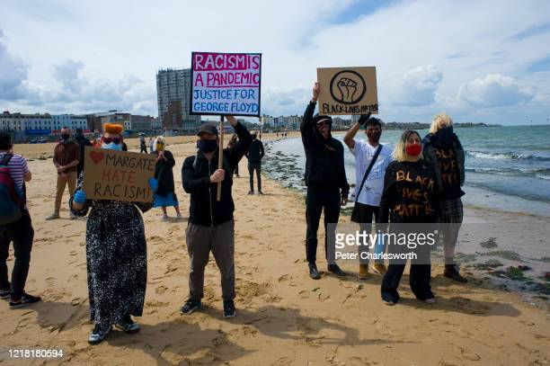 Protesters with placards listen to slogans being chanted by other demonstrators as they stand on the beach. Hundreds of local people joined a Black...