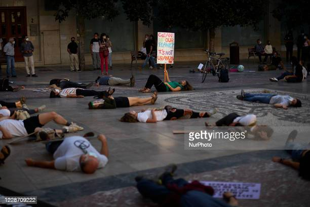 Protesters with signs with text Clean up our Planet, Its not Uranus are seen lying on the floor during a pacific concentration in Plaza del Carmen...