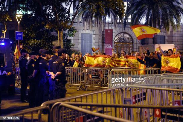 Protesters with Spanish flags shout slogans in favour of Spanish Constitution in front of Spanish National Police officers during a demonstration...