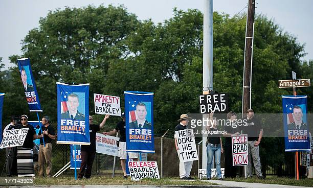 Protesters with the Bradley Manning Support Network hold a vigil while waiting to hear Manning's sentence on August 21 2013 outside the gate of Fort...