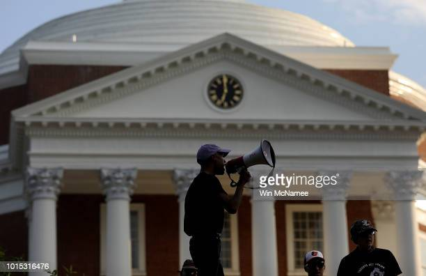 Protesters with the group Students Act Against White Supremacy speak on the campus of the University of Virginia during an event marking the one year...
