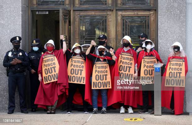 "Protesters with the ""Handmaids Brigade"" demonstrate outside the Dirksen Senate Office Building while a hearing held by the Senate Judiciary Committee..."