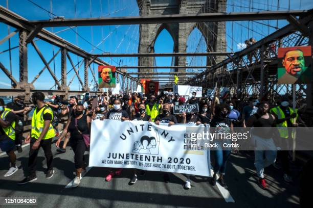 Protesters with the Unite NY Juneteenth 2020 organization walk a banner with thousands of protesters behind them holding signs and some holding...
