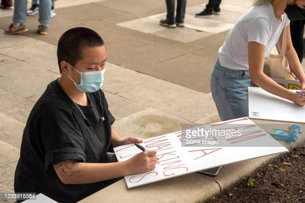 Protesters writes I am not a walking virus on a placard during a Stop Asian Hate protest at Parliament Square in London. Anti-Asian violence and...