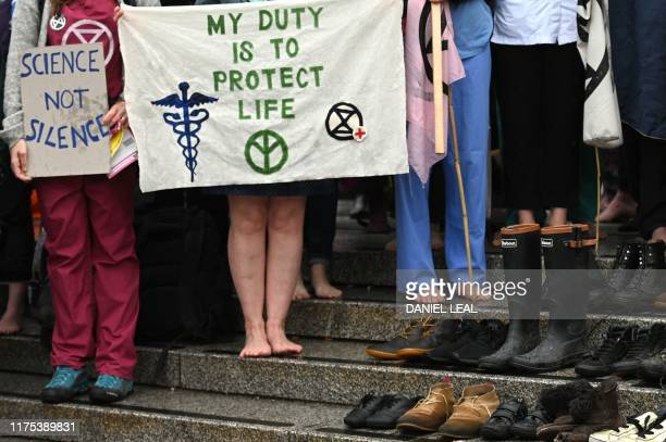 Protesting doctors stand barefoot alongside 180 pairs of shoes symbolising deaths due to pollution on the steps of Trafalgar Square during the sixth...