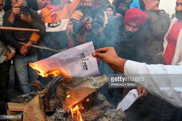 Protesting farmers burn copies of recent agricultural reforms bill while celebrating Lohri festival, as they continue to protest along a blocked...