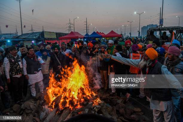 Protesting farmers celebrate Lohri festival around a bonfire, as they continue their protest along a blocked highway against the central government's...