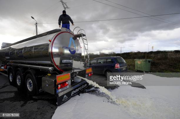 Protesting farmers empty milk from a refrigerated tanker coming from Portugal onto the ground during a protest action near the village of Monforte de...