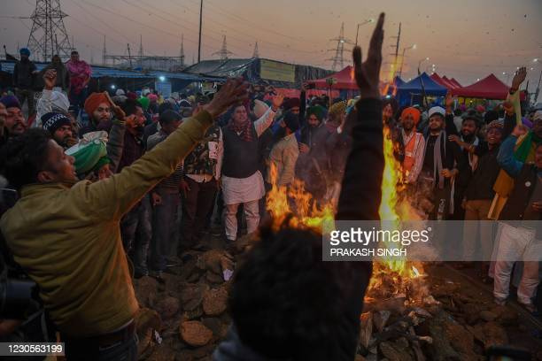 Protesting farmers shout slogans while burning copies of recent agricultural reforms bill while celebrating Lohri festival, as they continue to...