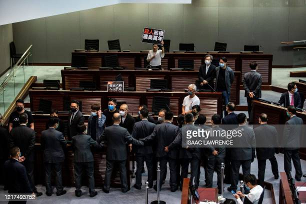 TOPSHOT Protesting prodemocracy lawmakers are blocked off by security during a debate on a law that bans insulting China's national anthem during a...