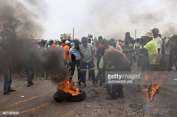 Protesting residents try to create a roadblock by dragging burning tyres into the main road leading into the town of Bronkhorstspruit during a...