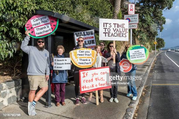 Protesting teachers wait for a bus to take them to a rally on August 15 2018 in Auckland New Zealand New Zealand primary school teachers and...