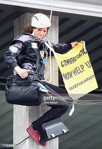 A protestor abseils from the roof to unveil a flag above the podium following the Belgian Grand Prix at Circuit de SpaFrancorchamps on August 25 2013...