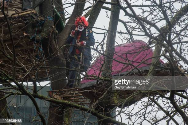 Protestor addresses the crowd below with a megaphone from a treehouse on January 27, 2021 in London, England. The eviction came after protesters...