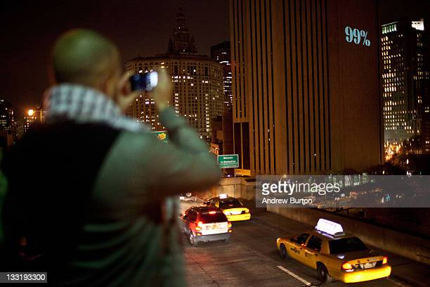 Protestor affiliated with the Occupy Wall Street Movement takes a photo of a projection of 99% on the Verizon building from the Brooklyn Bridge in...