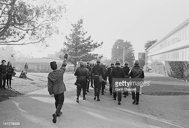 A protestor arm raised in a mock Nazi salute follows a San Francisco police tactical squad on the campus of San Francisco State College San Francisco...