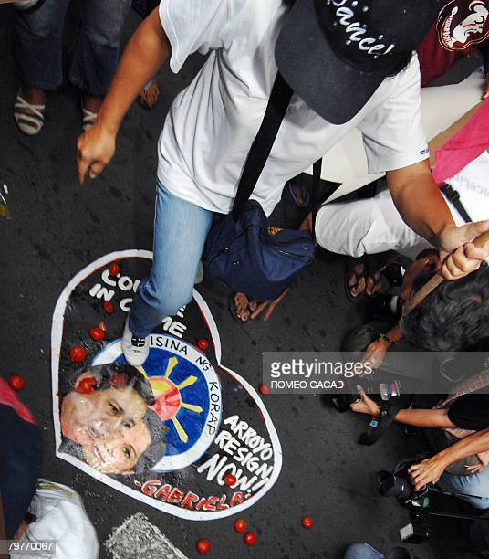 A protestor calling for resignation of President Gloria Arroyo steps on her portrait and that of her husband Jose Miguel Arroyo during a rally...