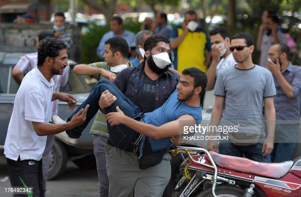 Protestor carries a fellow comrade near Rabaa al-Adawiya square in Cairo during clashes between supporters of Egypt's ousted president Mohamed Morsi...