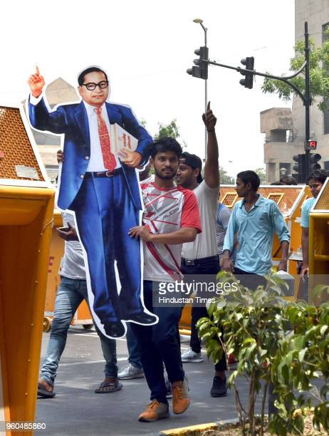 Protestor carries a giant cut-out of Dr. BR Ambedkar during a protest by the members of dalit and tribal community against atrocities demanding for...