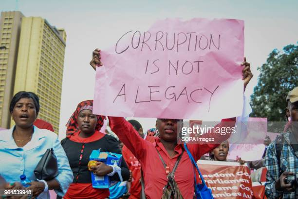 A protestor carries a placard as Kenyans protested in the streets of the capital city Nairobi Protesters took to the streets to call on the...