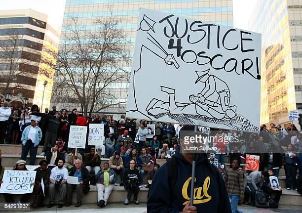A protestor carries a sign during a demonstration for slain 22yearold Oscar Grant III January 14 2009 in Oakland California Twelve days after the...