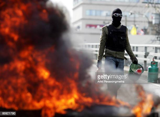 A protestor carries gasoline as he walks past burning tyres during a protest near Victory Monument on April 13 2009 in Bangkok Thailand Prime...